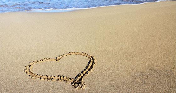 предложение руки и сердца на песке